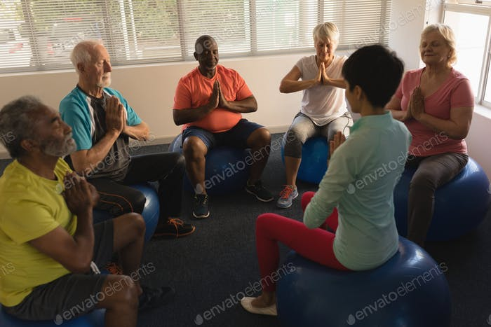Front view of female trainer training senior people in performing yoga with ball exercice  at home