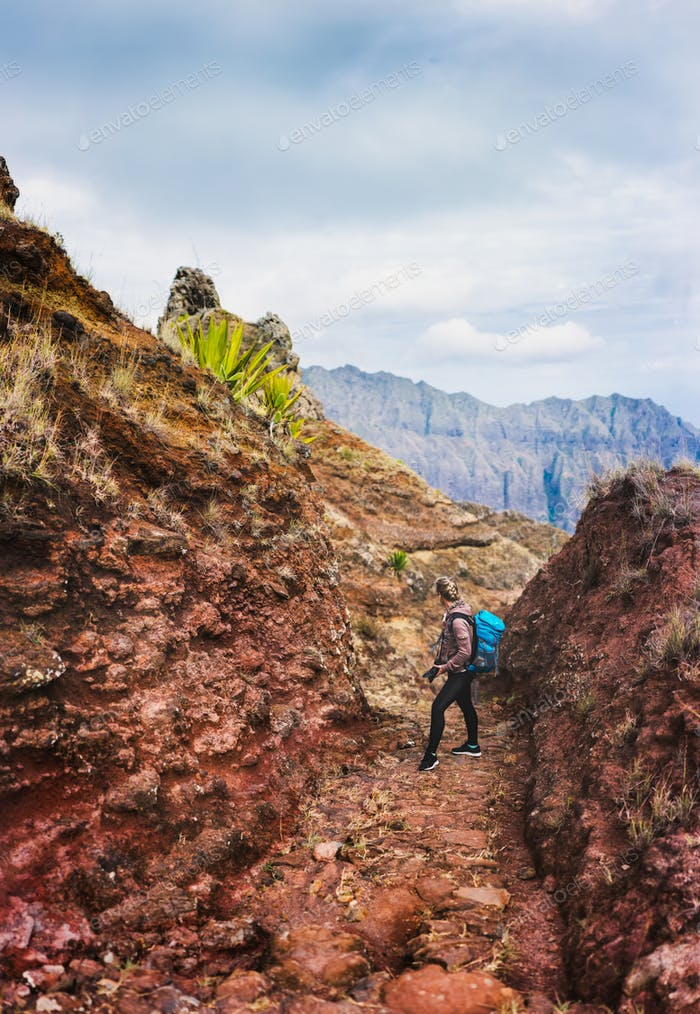 Female hiker with blue backpack staying on the stony cobbled trekking trail leading down to the Paul