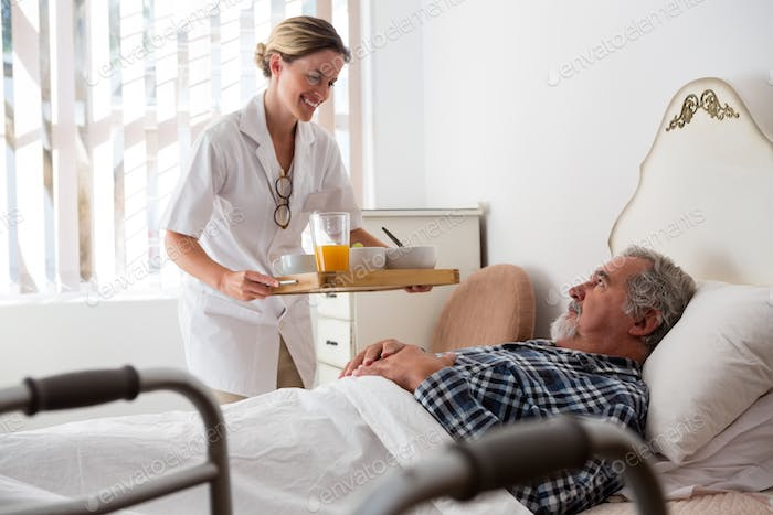 Female doctor serving food to senior patient relaxing on bed