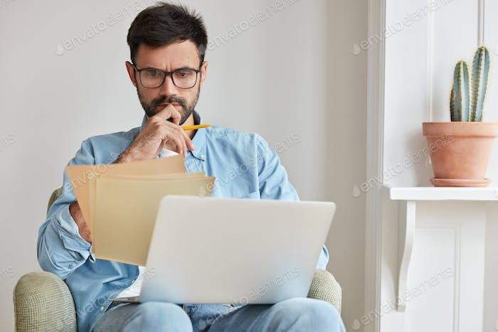 Serious concentrated businessman in spectacles for vision protection, works on laptop computer, stud