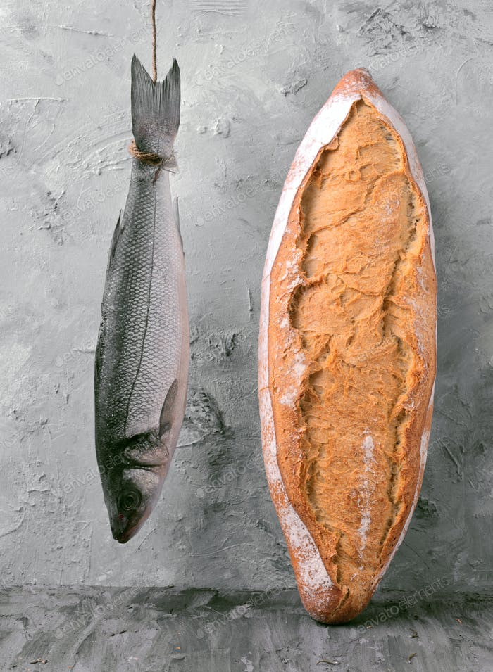 sea bass hanging on a rope with rustic bread, in front of gray marbling background