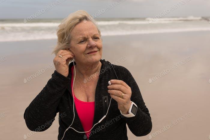 Happy senior woman wearing earphones at the beach