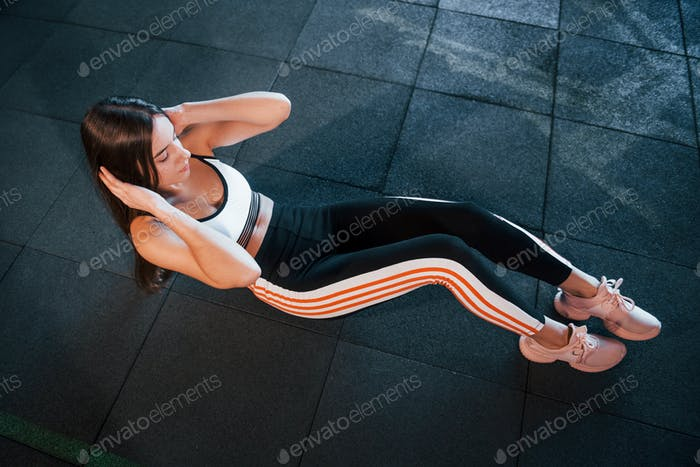 Young woman in sportive clothesdoing abs on floor in the gym