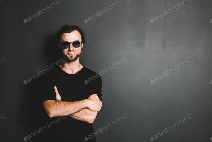 Portrait of smiling casual man standing on grunge wall.
