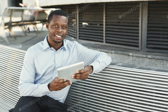 African-american businessman working with tablet outdoors