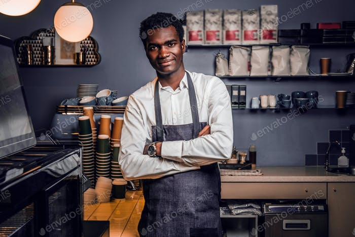 Barista standing with his arms crossed and looking at a camera in a coffee shop