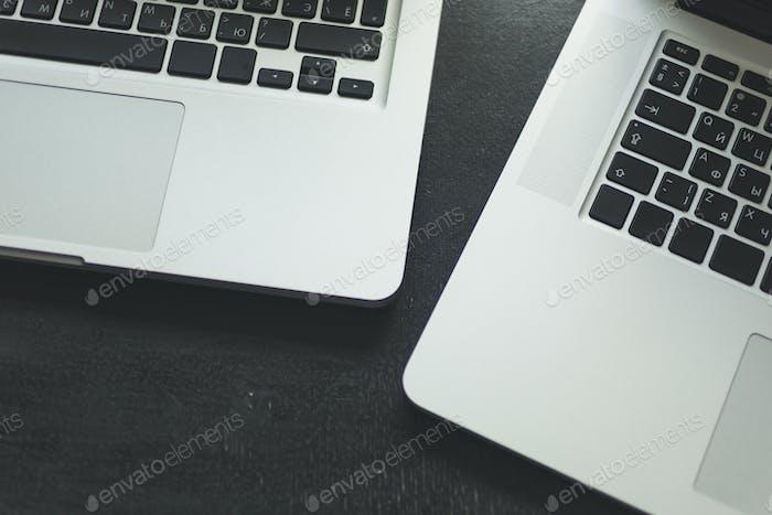 Two laptops on modern wooden desk