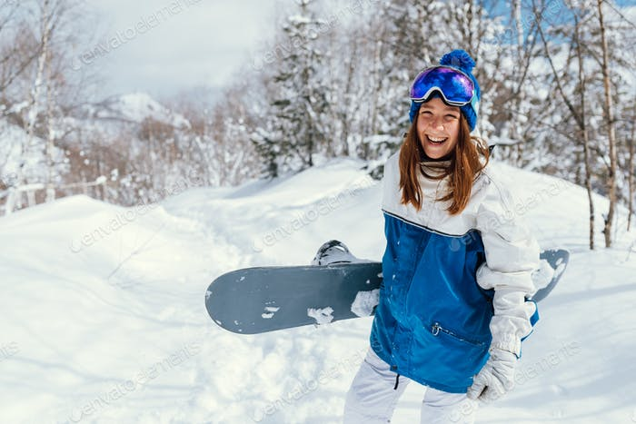 laughing happy girl with a snowboard and background of mountains