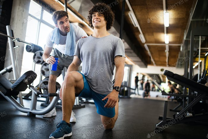 Young fit man doing workout with a personal trainer