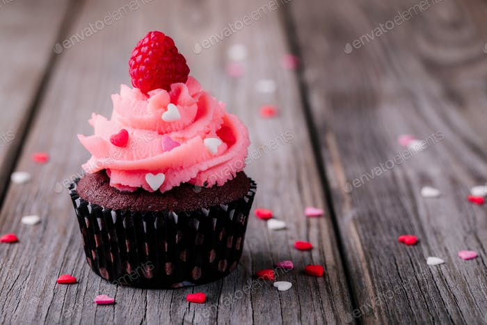 Chocolate cupcakes with pink cream, sugar hearts and fresh raspberries for  Valentine Day