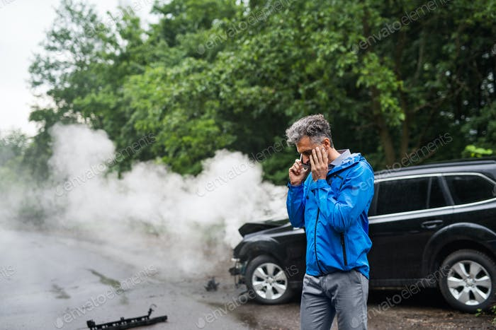 Mature man making a phone call after a car accident, smoke in the background.