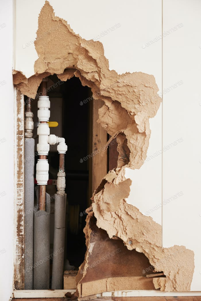 Damaged wall exposing burst water pipes after flood, vertical
