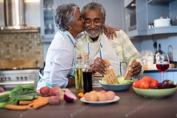 Senior woman kissing man while preparing food
