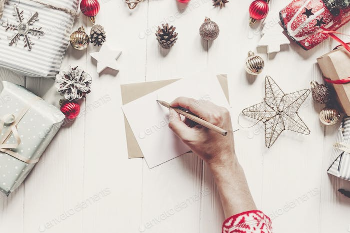 Hands holding pencil and writing a letter to santa claus