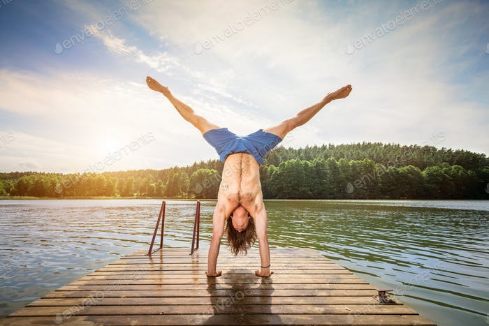 Young man doing a handstand on a wooden jetty