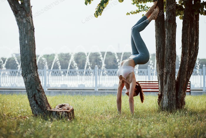 Fountain at background. Young woman with slim type of body does exercises in the park