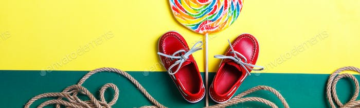 Banner of Small red boat shoes near big multi-colored lollipop and rope on colored background.
