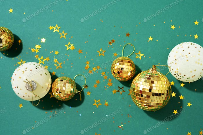 Christmas white and gold decorations, mirror disco balls, star sparkles over green background. Flat