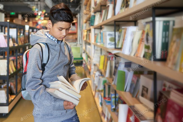 Student with backpack standing in library looking through books