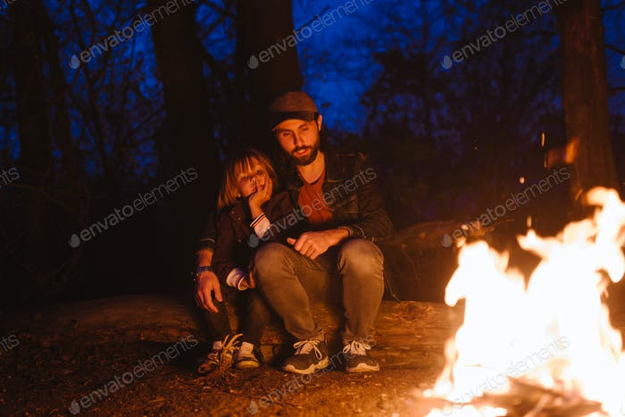 Happy father and his little son sitting together on the logs in front of a fire in a hike in the