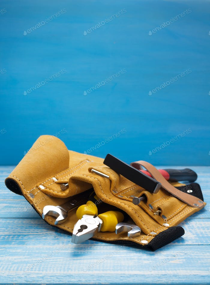 tools and instruments in belt on wooden table