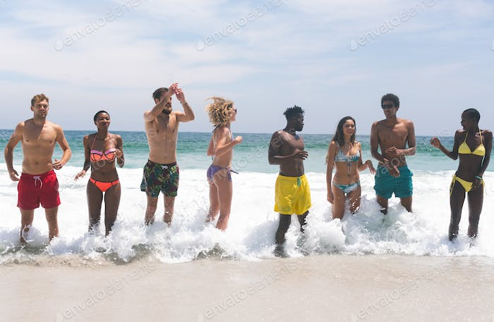 front view of multi-ethnic group of friends relaxing  and standing in water at beach on a sunny day
