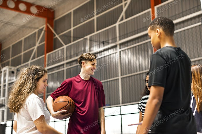 Group of teenager friends on a basketball court talking