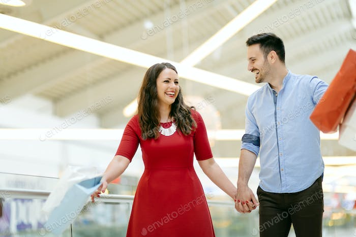 Happy shopper couple buying clothes