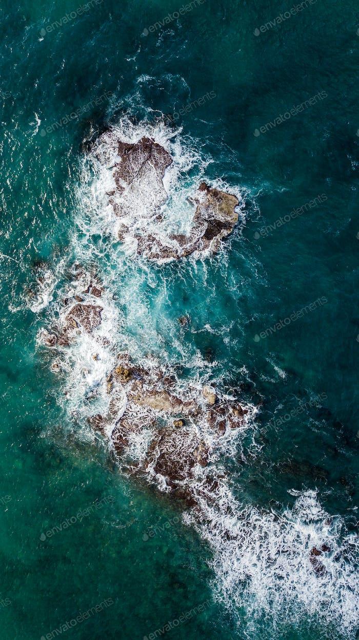 aerial view of waves crashing at rocks in blue sea, Tel Aviv, Israel