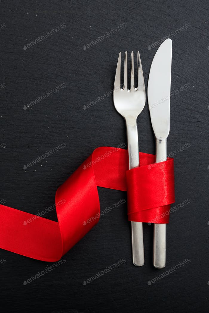 Valentine day dinner table setting. Fork and knife cutlery tied with red ribbon