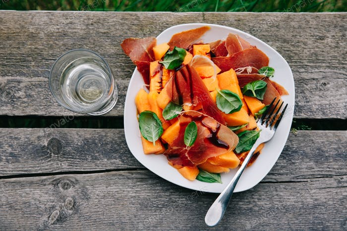 Prosciutto and melon salad with basil and balsamic sauce.