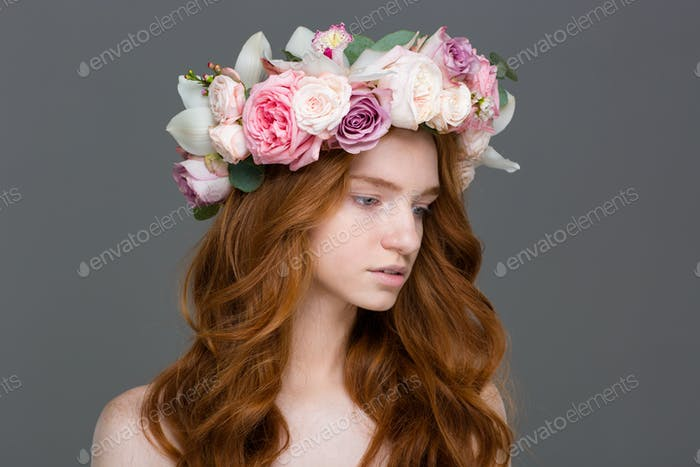 Beautiful tender woman with long hair in wreath of roses