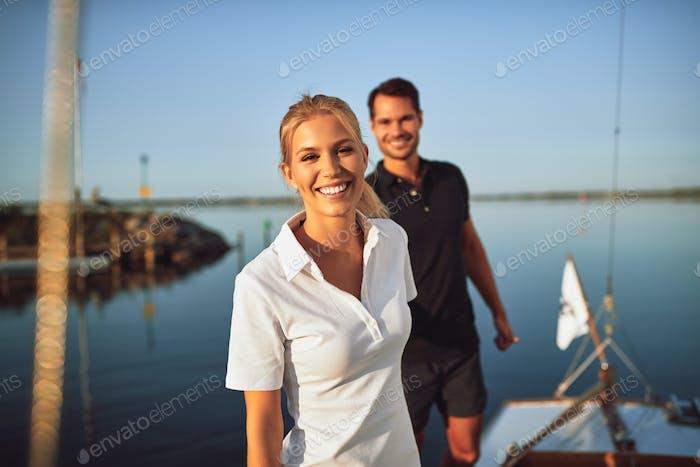 Lächelnde junge Frau stehend mit ihrem Mann auf ihrer Yacht