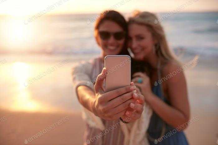 Weibliche Freunde nehmen selfie mit Strand Sonnenuntergang