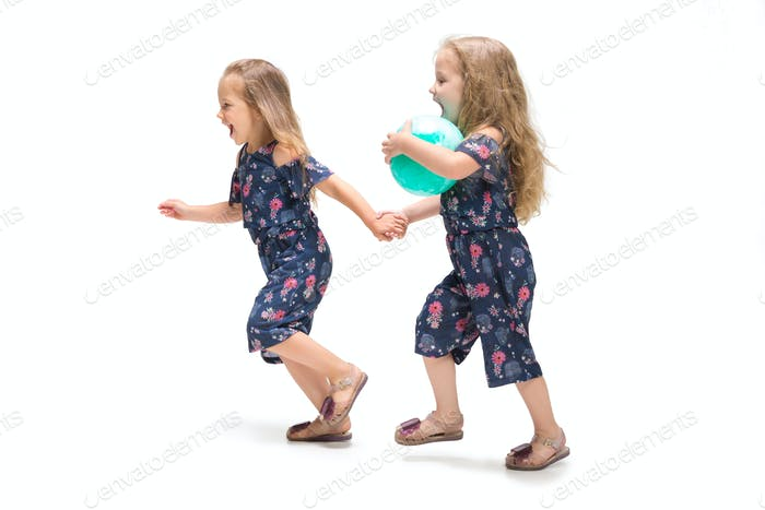 Smiling cute toddler girls three years running over white background