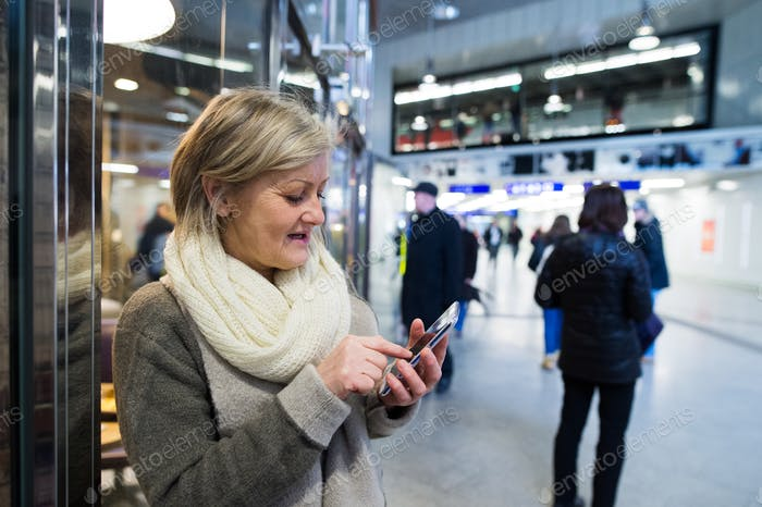 Senior woman with smartphone in hallway of subway