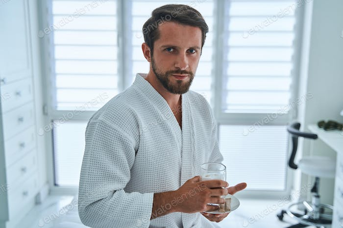Patient in a waffle weave bathrobe holding a non-alcoholic beverage