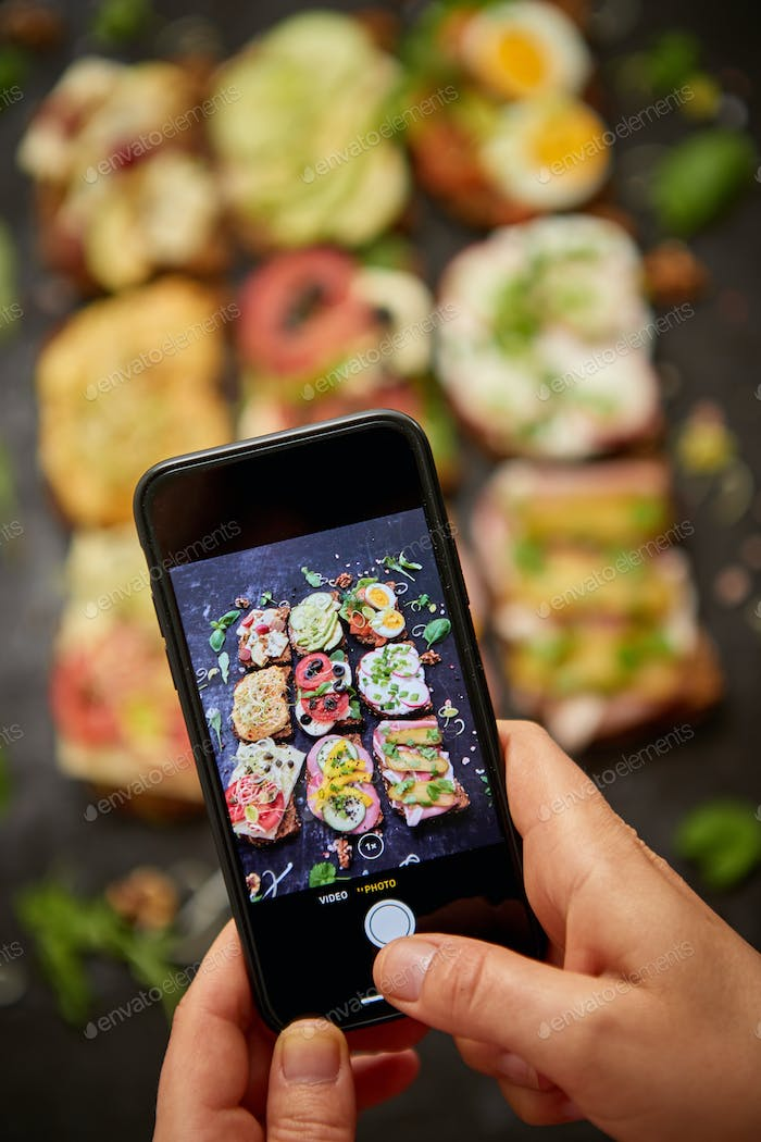 Woman making a photo with a smartphone of assortment of home made sandwiches with various toppings