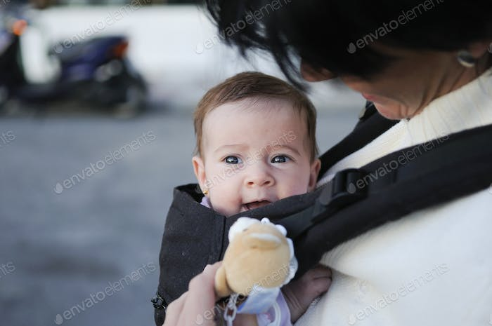 Mother carrying her baby girl in a baby carrier