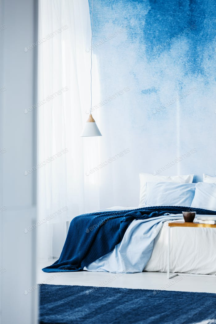 White lamp above bed with navy blue blanket in bedroom interior