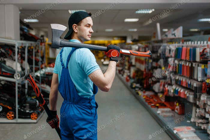 Male worker in uniform holds two axes, tool store