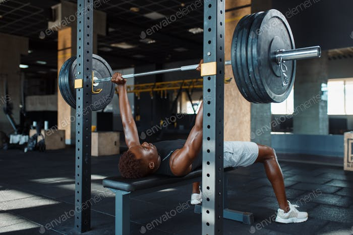 Muscular man doing exercise with barbell in gym