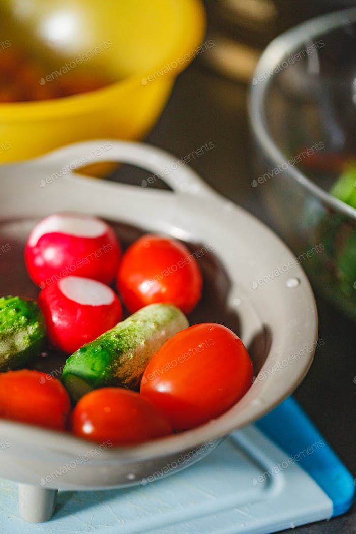 Various coloured organic vegetables washed in colander in kitchen
