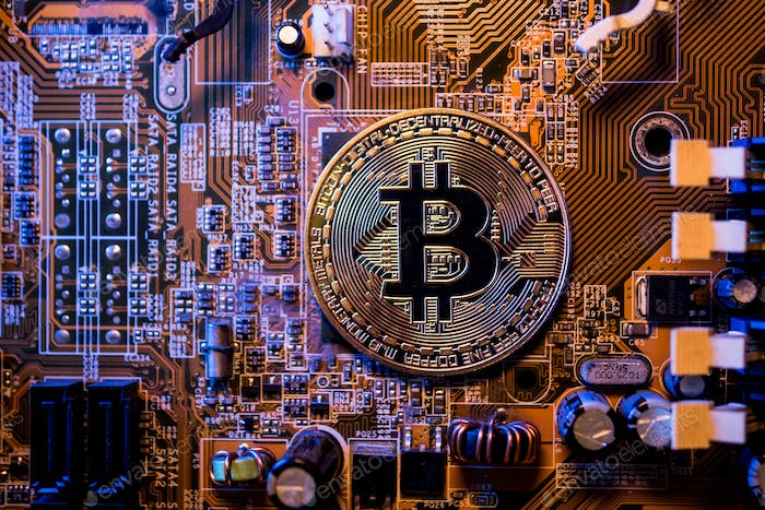 Golden coins with bitcoin symbol on a main board computer.