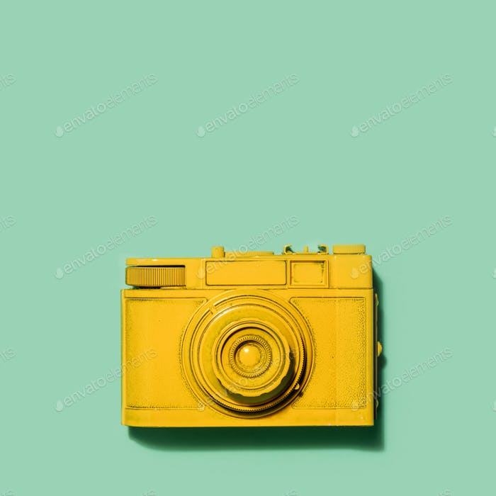 Yellow camera laying on a green background