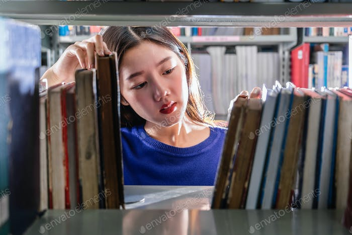 Asian young Student in casual suit searching the book in serious feeling from book shelf in library