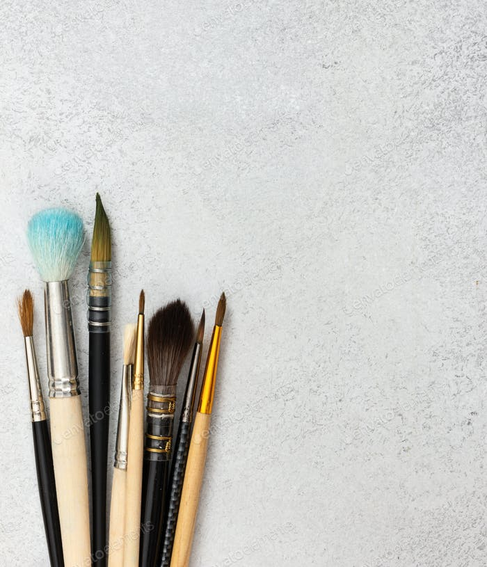 Artistic brushes on gray stone background.