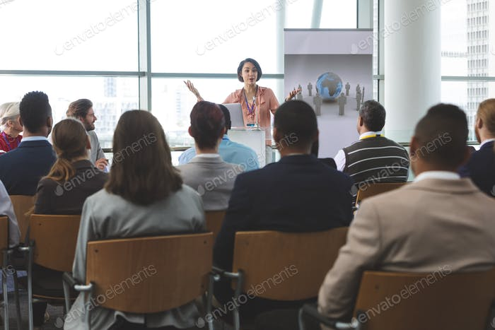 Businesswoman speaking animatedly to crowd of business people at business seminar in office