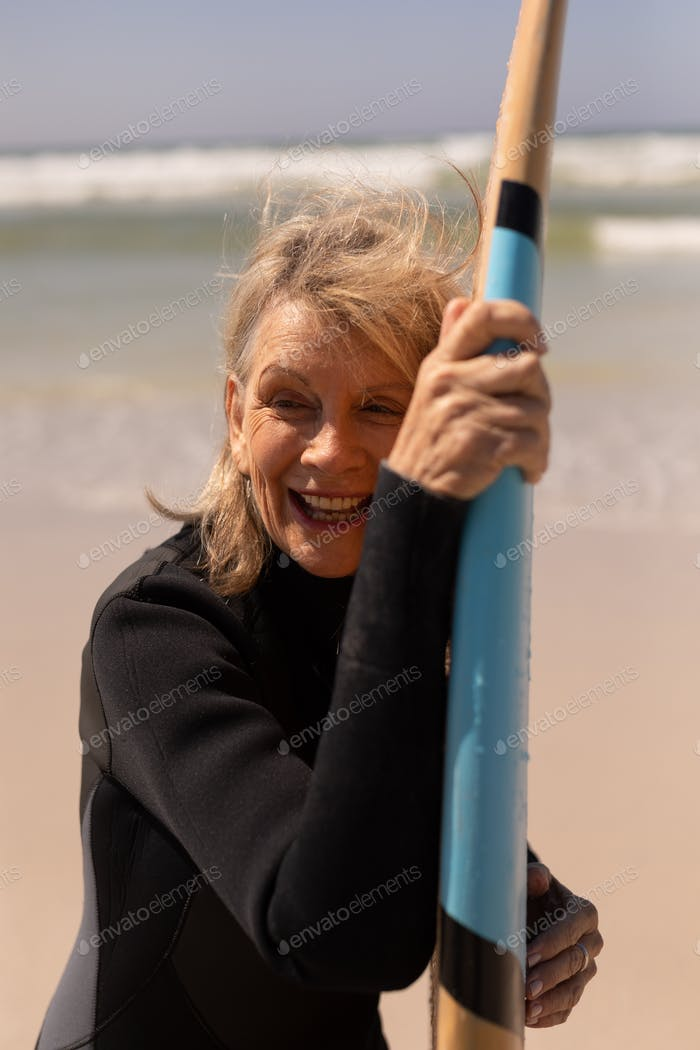 Front view of active senior female surfer standing with surfboard on the beach