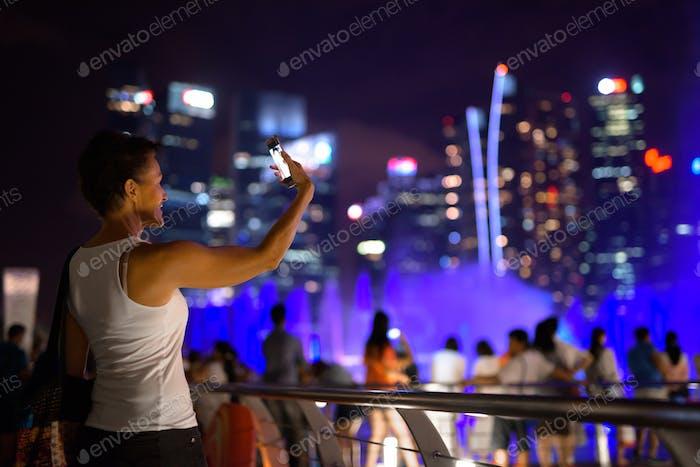 Glückliche reife schöne Touristenfrau unter Selfie in der Stadt in der Nacht